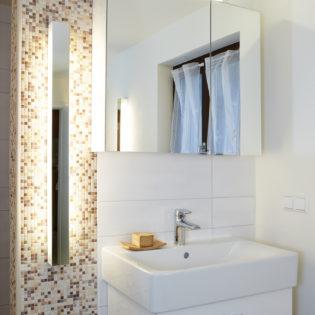 Mosaikfliesen und ein Spiegelschrank machen den Waschplatz zu einem optischen Hingucker im Bad