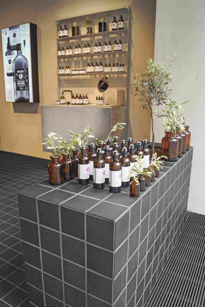 Die Präsentationstheke im Oliveda-Shop ist mit schwarzen Fliesen bekleidet, die auf die Wand- und Bodenfliesen abgestimmt sind.